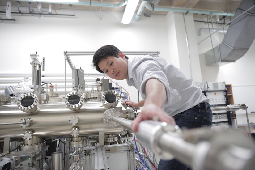 Jason Kawasaki adjusting a piece of metal equipment in his lab