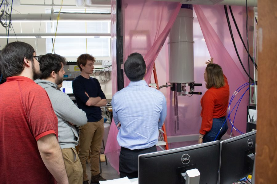 a group of students in a physics lab being shown a quantum computer