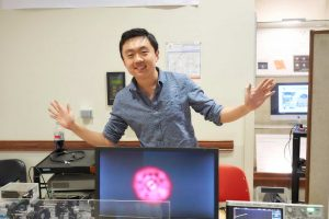 a male student poses with his arms out behind a computer screen