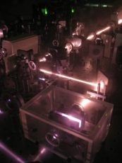 A dark room with pink-hued lasers reflecting off of mirrors