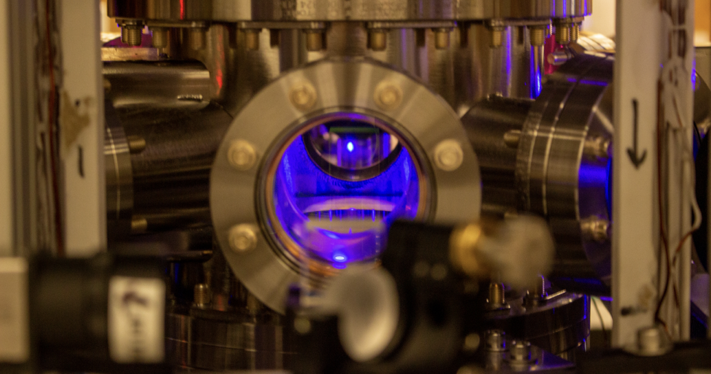 a metallic chamber with a blue fluorescence glowing orb of atoms in the center