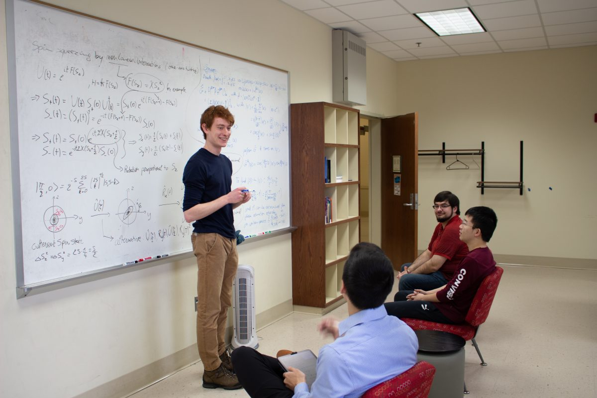 a group of students in front of a white board with physics equations on it